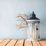 White wooden vintage lantern with burning candle and tree branches on wooden table Royalty Free Stock Images