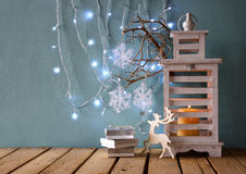 White wooden vintage lantern with burning candle and tree branches on wooden table. retro filtered image Stock Image