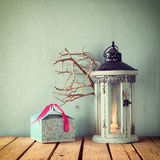 White wooden vintage lantern with burning candle and tree branches on wooden table. retro filtered image Royalty Free Stock Photo