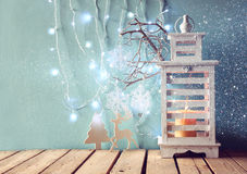 White wooden vintage lantern with burning candle and tree branches on wooden table. retro filtered image with glitter overlay Stock Images