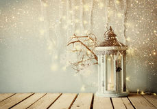 White wooden vintage lantern with burning candle and tree branches on wooden table. retro filtered image with glitter overlay Stock Photos
