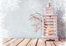 White wooden vintage lantern with burning candle and tree branches on wooden table. retro filtered image with glitter and snowflak Royalty Free Stock Images