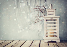 White wooden vintage lantern with burning candle and tree branches on wooden table. retro filtered image with glitter and snowflak Royalty Free Stock Image