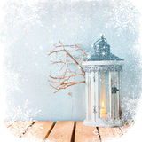 White wooden vintage lantern with burning candle and tree branches on wooden table. retro filtered image with glitter. Royalty Free Stock Photography