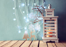 White wooden vintage lantern with burning candle, wooden deer, christmas gifts and tree branches on wooden table. retro filtered. Stock Images