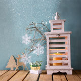 White wooden vintage lantern with burning candle, wooden deer, christmas gifts and tree branches on wooden table. retro filtered i Stock Image