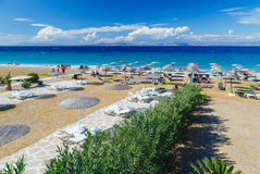 White wooden walkway on beach including umbrellas with deck chairs. Aegean Sea. Greece Rhodes. pebble Stock Images