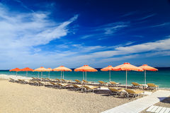 White wooden walkway on beach including umbrellas with deck chairs. Aegean Sea. Greece Rhodes. pebble beach Royalty Free Stock Images