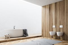 White and wooden bathroom corner. White and wooden wall bathroom corner with a white tub and two toilets. A gray carpet on a wooden floor. 3d rendering mock up Stock Images