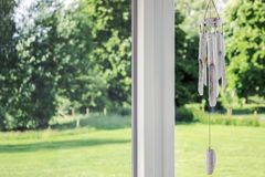 White wind chime with green plants. White wooden wind chime with green plants Royalty Free Stock Photos