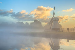 White wooden windmill in morning fog Royalty Free Stock Photos