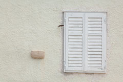White wooden window with closed slatted shutters Stock Photos