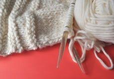 White wool knitting needles and handmade knits on bright orange background. White wool knitting needles and handmade knits on bright orange and red background Stock Photo