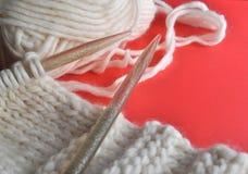 White wool knitting needles and handmade knits on bright orange background. White wool knitting needles and handmade knits on bright orange and red background Royalty Free Stock Photography