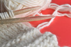 White wool knitting needles and handmade knits on bright orange background. White wool knitting needles and handmade knits on bright orange and red background Royalty Free Stock Photo