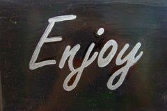 White word enjoy on black background Royalty Free Stock Images