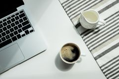 Working desk with laptop computer and cup of black coffee and tablecloth Royalty Free Stock Photo