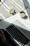 Working desk with laptop computer and cup of black coffee and tablecloth Stock Images