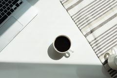 Working desk with laptop computer and cup of black coffee and tablecloth Stock Image