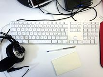 White workspace desk. With a computer keyboard, a pen, a note and headphones stock image