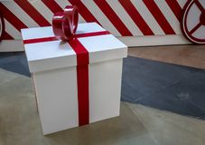White wrapped present box with red bow tie against concrete back stock photography