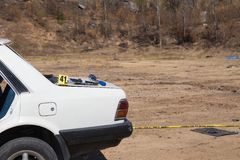 White wrecked car from car bomb with forensic tool and police l. White wrecked car from car bomb with evidence marker and forensic search tool with police line Stock Photos