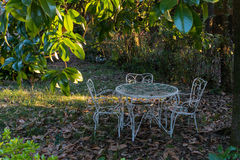White  wrought iron table and two chairs abandoned  under a magn Stock Photography