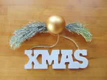 White Xmas letters with christmas decoration on wood. White Xmas letters with christmas ball and pine above royalty free stock photos