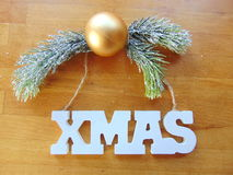 White Xmas letters with christmas decoration on wood. White Xmas letters with christmas ball and pine above stock images