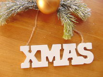 White Xmas letters with christmas decoration on wood. White Xmas letters with christmas ball and pine above Royalty Free Stock Photography