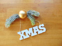 White Xmas letters with christmas decoration on wood. White Xmas letters with christmas ball and pine above Royalty Free Stock Image