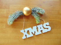 White Xmas letters with christmas decoration on wood. White Xmas letters with christmas ball and pine above Stock Photography