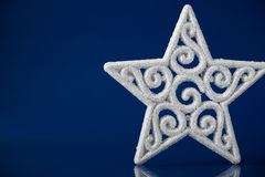 White xmas star on dark blue christmas background with space for text Royalty Free Stock Photos