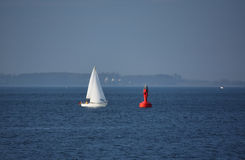 White Yacht approaching Red Buoy. On the blue Ocean Stock Photo