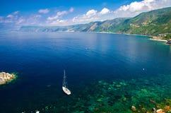 White yacht in blue lagoon near small fishing village, Calabria, Italy stock photos