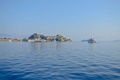 White yacht and the fortress of Corfu. A white yacht in the front and fortress of Corfu in the background, Greece - Europe Royalty Free Stock Photography