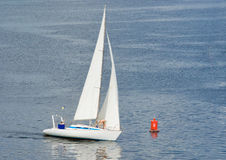 White yacht making a close turn near buoy Royalty Free Stock Photos