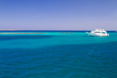 The white yacht moored beside the island Paradise Stock Images