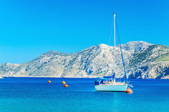 White yacht moored in sea bay of Greek Island Royalty Free Stock Photo