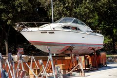 White yacht motor boat in the harbor. Yacht motor boat in the harbor. White yacht motorboat on the maintenance structure at the harbor. Wooden yacht out of the Royalty Free Stock Images