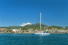White yacht near beach with mountains at back Royalty Free Stock Image