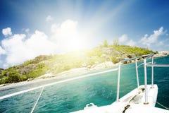 White yacht near rocky coast of seychelles. Stock Photo