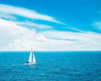 White Yacht Sailing in Blue Sea. Beautiful Clouds. Royalty Free Stock Image