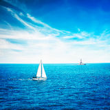 White Yacht Sailing in Calm Blue Sea. Lighthouse. Royalty Free Stock Image