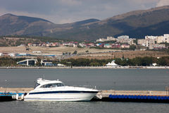 White yacht at the sea mooring. City in the background Royalty Free Stock Photos