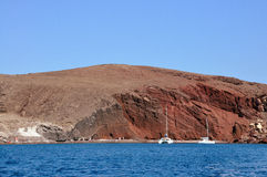 White yachts and the famous Red beach in Santorini island, Greece. White yachts on the background of terracotta rock and blue sky. The famous Red beach, in Royalty Free Stock Photography