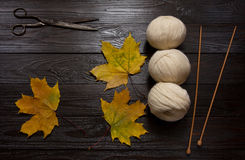 White yarn, wooden knitting needles, scissors, yellow leaves. Three skeins of white yarn, wooden knitting needles, scissors and yellow leaves are a dark wooden stock photos