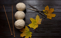 White yarn, wooden knitting needles, scissors, yellow leaves. To. Three skeins of white yarn, wooden knitting needles, scissors and yellow leaves are a dark Royalty Free Stock Photography