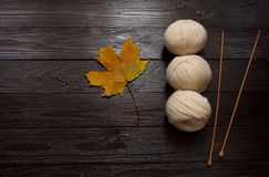 White yarn, wooden knitting needles, yellow leaves on dark table. Three skeins of white yarn, wooden knitting needles, yellow leaves are a dark brown wooden Stock Photo