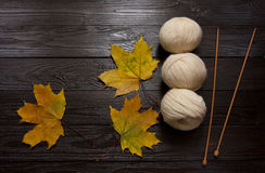 White yarn, wooden needles, yellow leaves on dark wooden table. Three skeins of white yarn, wooden knitting needles, yellow leaves are a dark brown wooden table Stock Image